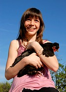 laughing girl and her little little black chicken in a farm