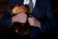 A businessman in a suit and tie holds a teddy bear in his arms. Horizontal shot.