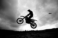 Dirt bike rider jumping sand dunes against an ominous dark cloudy sky.