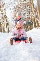 Boy And Girl Sledging Through Snowy Woodland