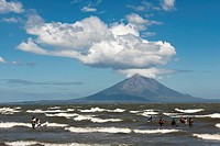 People walking on the shallow shore of Lago de Nicaragua, volcanic island of Ometepe and the stratovolcano Volcán Concepión at back, San Jorge, Nicara...