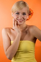 young beauty blond girl with yellow top and hair style with gerbera and orange background