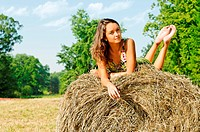 Rural landscape with Young beautiful woman at the haystack