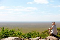 Young woman observing beautiful national park of Serengeti in Tanzania