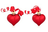 Christmas heart shaped red baubles with ribbons, isolated over white background.