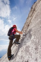 Mountaineer climbing on the Che Guevara fixed rope route on Monte Casale mountain, Sarca valley, Lake Garda region, province of Trento, Italy, Europe