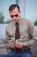 businessman in sunglasses counting the money on the street