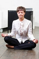 Businesswoman sitting on floor in yoga pose at break