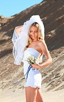 Beautiful bride in her white dress on a windy summer day