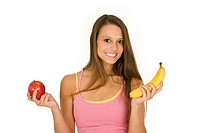 Caucasian woman holding an apple and a banana trying to decide which one to eat