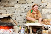 Smiling woman sitting in home bakery making bread