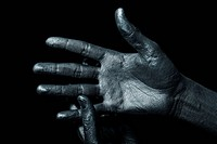 Men´s hand in a silver paint isolated on black background
