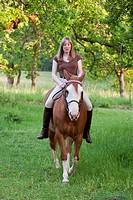 Pretty woman riding her horse bareback