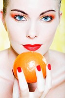 beautiful woman portrait with colorful make_up and background holding a mandarin