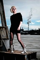 blond girl posing in a urban setting in front of an old factory