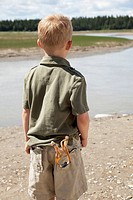 Rear view of a little boy with a slingshot in his pocket, looking across a lake.