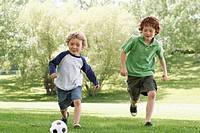 Two young boys play soccer in the park.