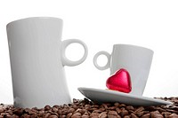 Two coffee cups with a small red chocolate heart