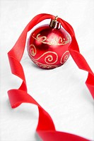 Red Christmas Bauble and red ribbon over white background