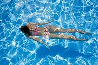 Woman in a polka dot bikini swimming underwater