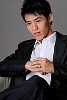 Closeup portrait of young business man sit on chair.
