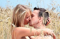 A beautiful couple sitting an kissing in wheat field