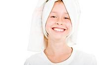 Blondes Mädchen hat sich ein Handtuch um ihre nassen Haare gebunden und grinst heiter