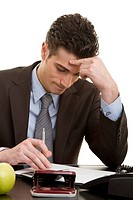 Junger Mann im Anzug am Schreibtisch zerbricht sich an einer Aufgabe den Kopf