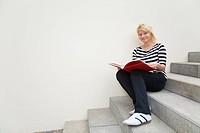 Junge Frau sitzt auf einer Treppe und liest ein Buch