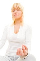 Junge Frau meditiert im Schneidersitz mit geschlossenen Augen