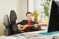 Mann im Anzug legt seine Füße auf den Schreibtisch und spielt Gitarre