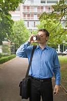 Mann in Geschäftskleidung steht auf einem Parkweg und trinkt Kaffee aus einem Pappbecher