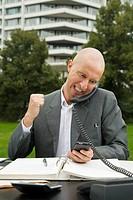 Geschäftsmann sitzt in einem Park an einem Schreibtisch und schaut auf einen PDA während er wütend telefoniert