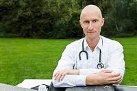 Arzt sitzt an einem Schreibtisch auf einer Wiese und schaut aufmerksam in die Kamera