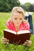 Blondes Mädchen liest liegend ein Buch im Park