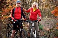 two cyclist biking in autumn forest