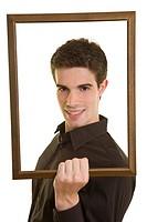 Junger Mann hält einen Holzrahmen vor sein Gesicht