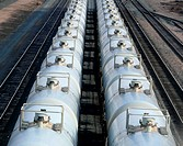 Clean white tanker cars sitting on railroad tracks.
