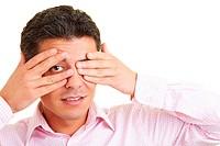 Mann hält Hände vor sein Gesicht und späht durch die Finger