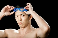Swimmer putting on swimming goggles