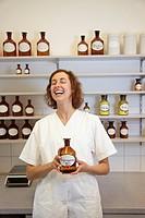 Lachende Apothekerin hält ein Glas mit Isopropanol