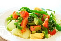 Fresh salad with cucumber, tomato, peppers, baby sweet corn and broccoli on white plate
