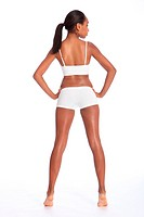 Behind view of a beautiful healthy young african american woman wearing white sports underwear, standing against white background showing off fit body...