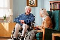 Senior couple in care home, man in wheelchair