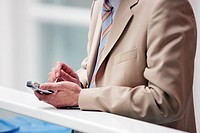 Businessman writing a message on his mobile_phone