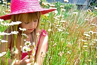 Little girl with hat in wild daisies.