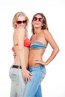 two young happy female friends in bikini tops smiling- isolated on white