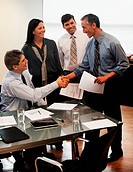 Businessman shaking hands in office with colleagues