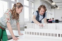Germany, Bavaria, Munich, Architects looking at architectural model, colleagues working in background