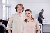 Germany, Bavaria, Munich, Man and woman standing in office, smiling, portrait